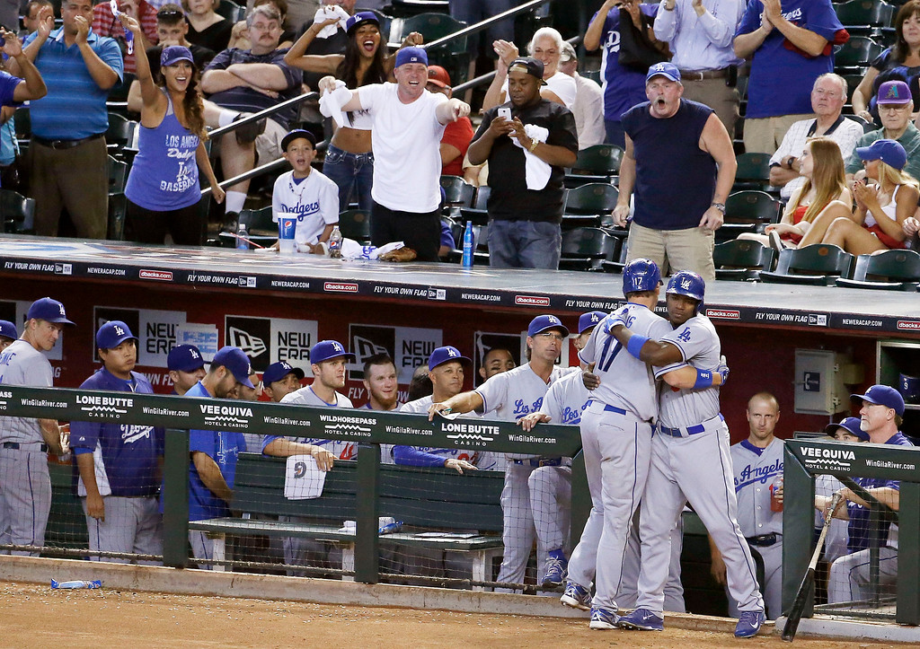 . As Los Angeles Dodgers fans cheer, Dodgers\' A.J. Ellis (17) gets a hug from Yasiel Puig, right, after Ellis hit a home run in the eighth inning of a baseball game against the Arizona Diamondbacks on Thursday, Sept. 19, 2013, in Phoenix.  The Dodgers defeated the Diamondbacks 7-6. (AP Photo/Ross D. Franklin)