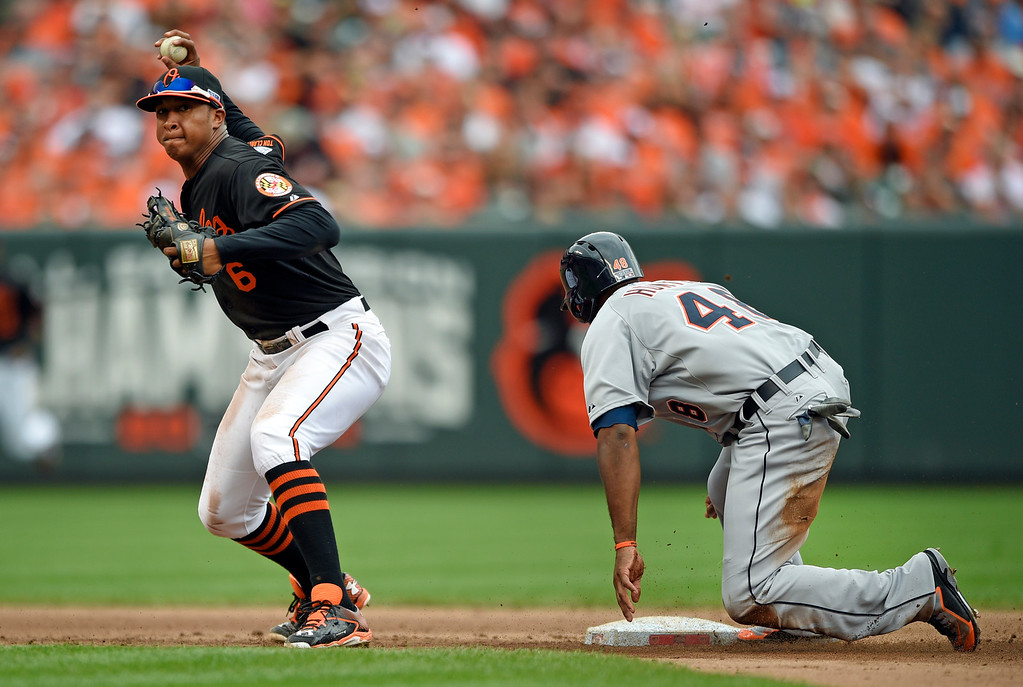 . Baltimore Orioles second baseman Jonathan Schoop, left, throws to first base for a double play after forcing out Detroit Tigers\' Torii Hunter on a ground ball by Miguel Cabrera in the fifth inning of Game 2 in baseball\'s AL Division Series in Baltimore, Friday, Oct. 3, 2014. (AP Photo/Nick Wass)