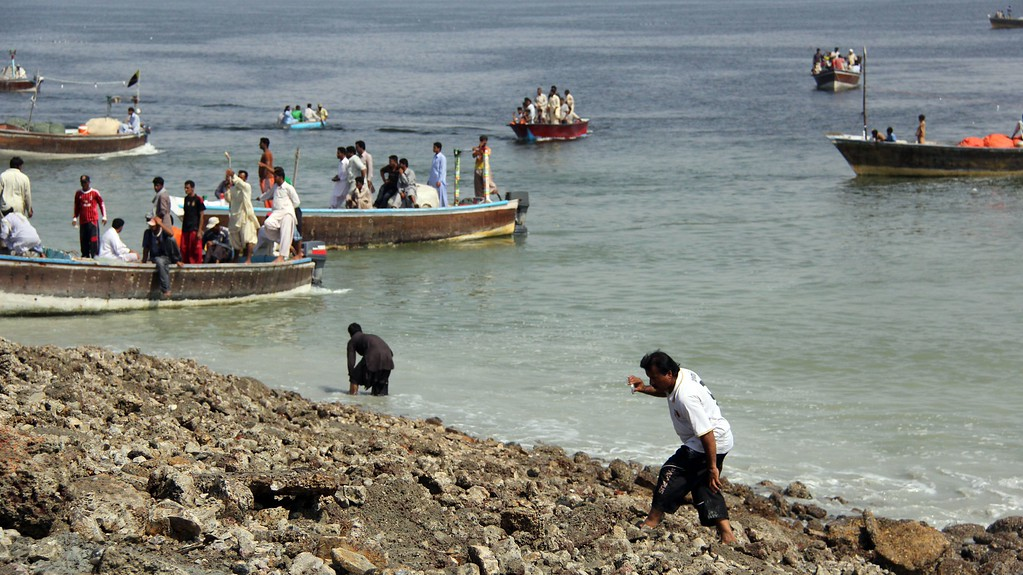 . This photograph taken on September 25, 2013, shows Pakistani residents as they arrive by boat to an island that appeared some two kilometres off the coastline at Gwadar after an earthquake. A small island of mud and rock created by the huge earthquake that hit southwest Pakistan has fascinated locals but experts -- who found methane gas rising from it -- say it is unlikely to last long. The 7.7-magnitude quake struck on September 24, in Baluchistan\'s remote Awaran district, killing at least 271 people and affecting hundreds of thousands. AFP PHOTO / Behram BALOCH/AFP/Getty Images
