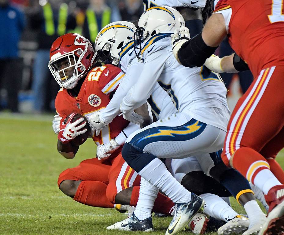. Kansas City Chiefs running back Kareem Hunt (27) is tackled by Los Angeles Chargers defenders during the second half of an NFL football game in Kansas City, Mo., Saturday, Dec. 16, 2017. (AP Photo/Ed Zurga)