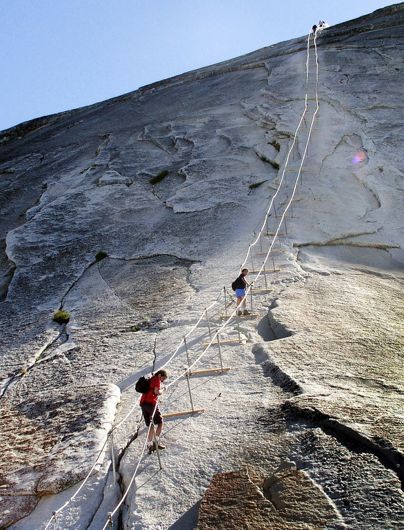 . n this June 6, 2004 photo, hikers descend the cable route after climbing to the summit of Half Dome, in Yosemite National Park. The trail of dirt and hundreds of feet of twisted metal cables might not immediately conjure an image of something worthy of historical preservation. But when the trail leads to the iconic Half Dome in Yosemite National Park and the cables allow armchair wilderness lovers to ascend the once-inaccessible granite monolith, the significance becomes enough for listing on the National Register of Historic Places.  (AP Photo/Robert F. Bukaty)