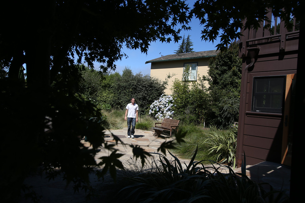 . Designer Dan Tiraschi, of Gustave Carlson Design in Berkeley, walks through the yard of a remodeled 1937 one-bedroom cabin on Woodmont Avenue in Berkeley, Calif., on Thursday, July 25, 2013. Carlson managed the project. (Jane Tyska/Bay Area News Group)