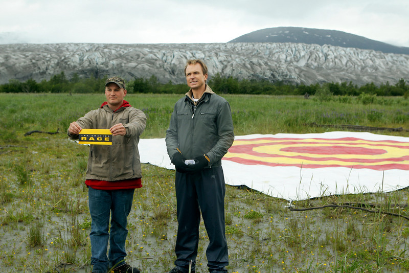 . Emmy award winning host Phil Keoghan (right) stands at the Road Block in Juneau, Alaska.  Teams must drop a sack a flour from a bush plane hundreds of feet in the air and hit the target below in order to receive the next clue on THE AMAZING RACE Sunday, Dec. 8 (8:00-10:00 PM, ET/PT) on the CBS Television Network. Photo: Monty Brinton/CBS©2013 CBS Broadcasting, Inc. All Rights Reserved