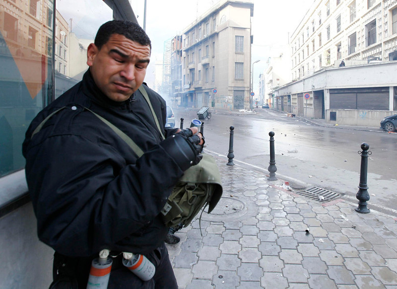 . A police officer reacts after teargas was used to break up a protest in Tunis February 6, 2013. Tunisian police fired teargas to disperse protesters demonstrating in the capital outside the Interior Ministry against the killing of a prominent secular opposition politician on Wednesday, witnesses said. REUTERS/ Anis Mili