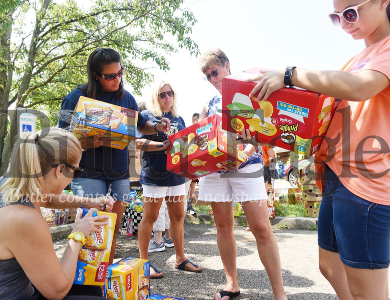 Harold Aughton/Butler Eagle: Volunteers label boxes of food during the Stuff A Bus event sponsored by the Golden Tornado Scholastic Foundation Tuesday, July 9.