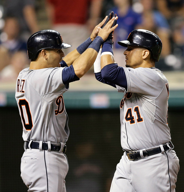 . Detroit Tigers\' Eugenio Suarez, left, congratulates Victor Martinez after Martinez hit a three-run home run off Cleveland Indians relief pitcher Josh Tomlin in the 11th inning of a baseball game, Thursday, Sept. 4, 2014, in Cleveland. The Tigers defeated the Indians 11-4. (AP Photo/Tony Dejak)