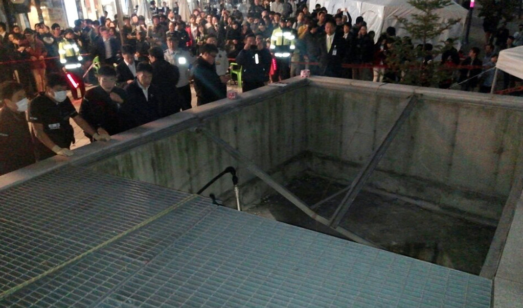 . A South Korean rescue team checks a broken ventilation grate in Seongnam City, near Seoul, after concert goers fell through it into an underground parking area below, on October 17, 2014.  AFP PHOTO/YONHAPYONHAP/AFP/Getty Images