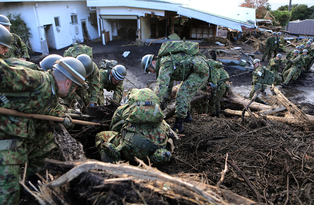 . Japan\'s Ground Self Defense Force soldiers remove debris to search for survivors after a landslide buried houses caused by heavy rain of typhoon Wipha at Oshima island, 120km south of Tokyo on October 16, 2013.  AFP PHOTO / JIJI PRESS /AFP/Getty Images
