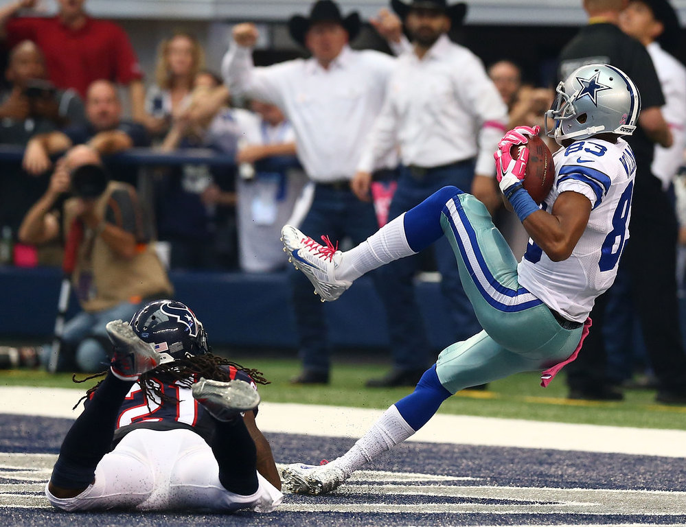 . Terrance Williams #83 of the Dallas Cowboys makes a catch for a touchdown as he is defended by Kendrick Lewis #21 of the Houston Texans in the second half at AT&T Stadium on October 5, 2014 in Arlington, Texas.  (Photo by Ronald Martinez/Getty Images)