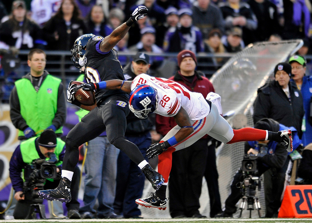 . New York Giants free safety Antrel Rolle (26) knocks Baltimore Ravens running back Bernard Pierce, left, out of bounds as Pierce was rushing the ball in the first half of an NFL football game in Baltimore, Sunday, Dec. 23, 2012. (AP Photo/Gail Burton)