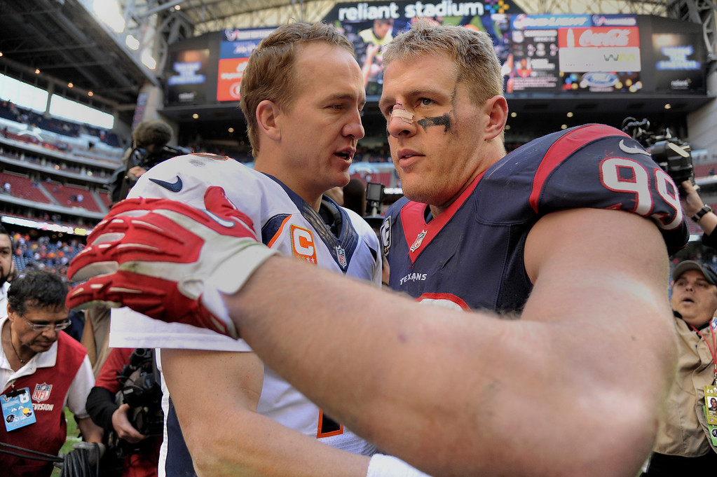 . Denver Broncos quarterback Peyton Manning (18) shakes hands with Houston Texans defensive end J.J. Watt (99) after their win 37-13 December 22, 2013 at Reliant Stadium. (Photo by John Leyba/The Denver Post)