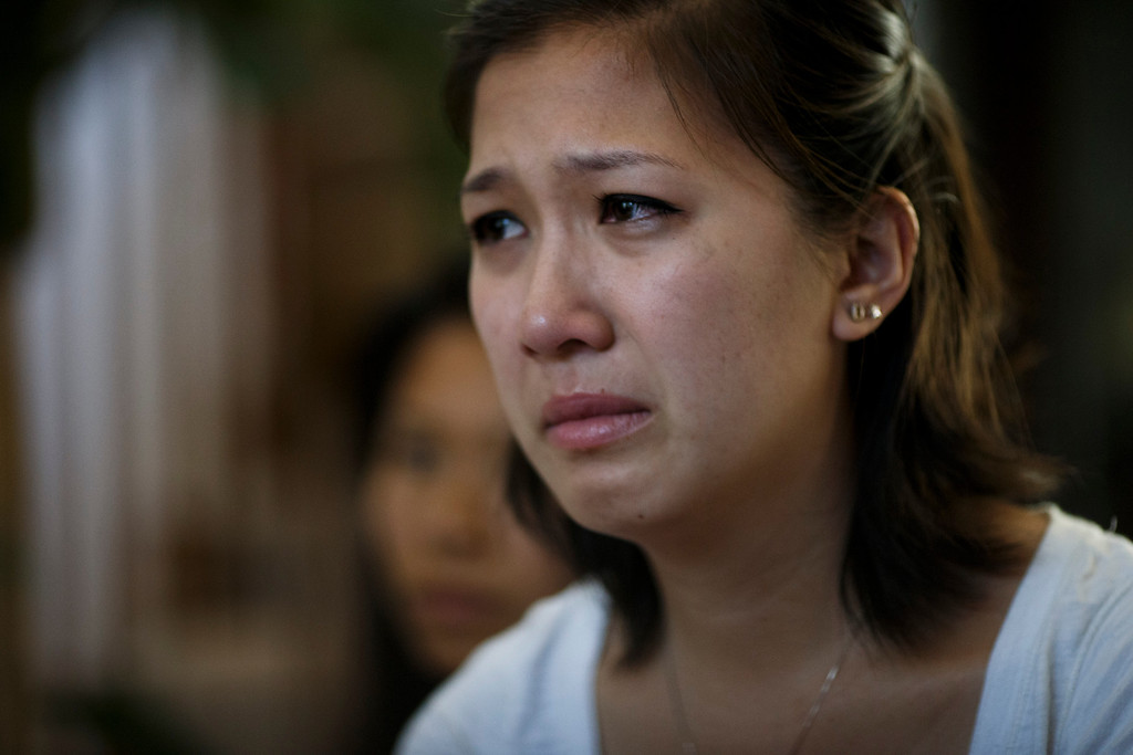 . Dalena Nguyen, center, is overwhelmed with emotion as she and her sisters, talk about their brother, Vince Canh Xuan Nguyen, to this newspaper on July, 16, 2013 at their mother\'s San Jose home.  The San Jose family believes there may be foul play behind the death of Vince Canh Xuan Nguyen, shown in a photo at right, who passed away in a tiny hotel room in Vietnam on July 1, 2013, after a night of drinking ended with him gravely ill, unable to control his body functions. (Dai Sugano/Bay Area News Group)