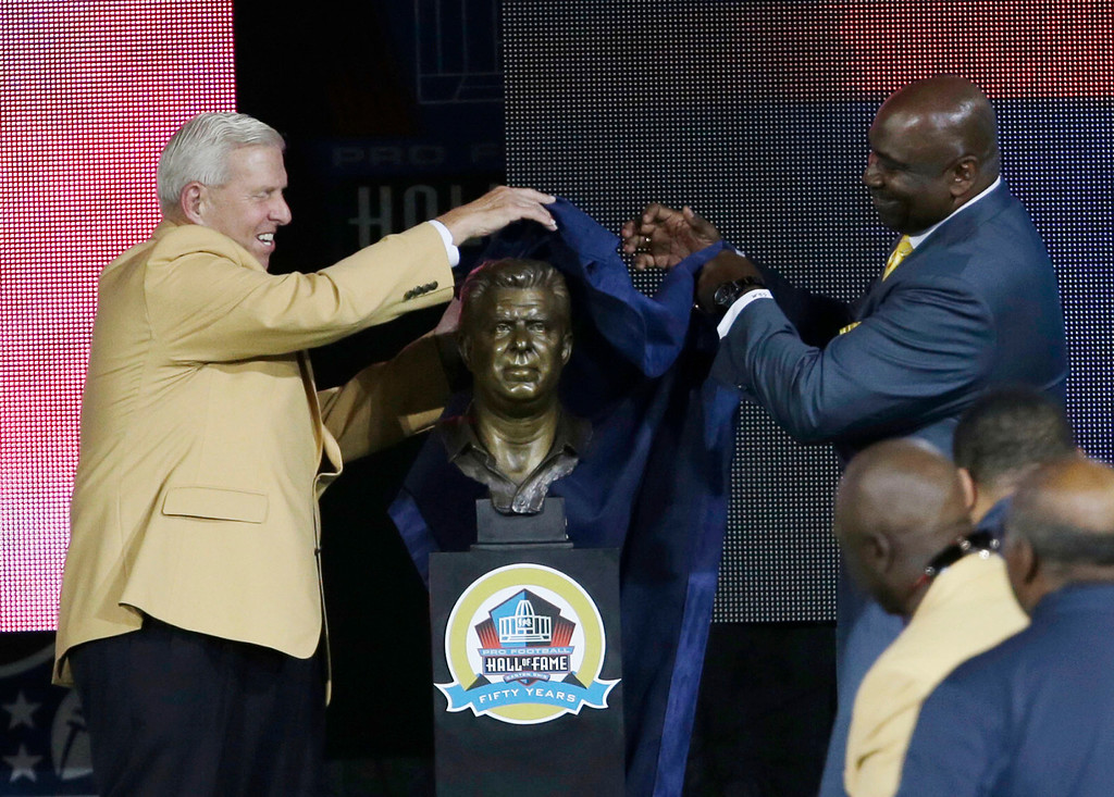 . Former NFL football head coach Bill Parcells, left, and his presenter, the former New York Giants player George Martin unveil a bust of Parcells during the induction ceremony at the Pro Football Hall of Fame Saturday, Aug. 3, 2013, in Canton, Ohio. (AP Photo/Tony Dejak)