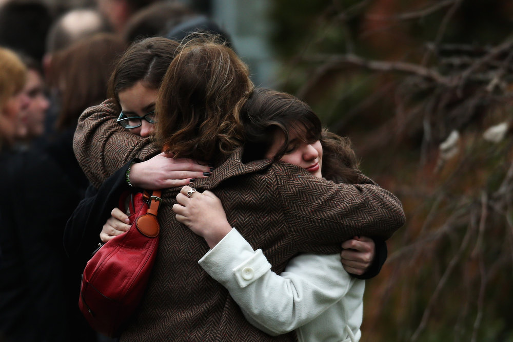 Description of . Three women embrace as they arrive for the funeral services of six year-old Noah Pozner, who was  killed in the shooting massacre in Newtown, CT, at Abraham L. Green and Son Funeral Home on December 17, 2012 in Fairfield, Connecticut. Today is the first day of funerals for some of the twenty children and seven adults who were killed by 20-year-old Adam Lanza on December 14, 2012.  (Photo by Spencer Platt/Getty Images)