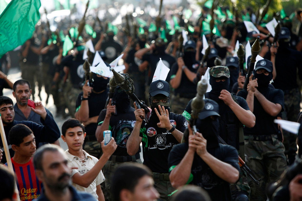 . Masked Palestinian members of the Ezz Al-Din Al Qassam brigade, the military wing of Hamas, march with their weapons during a parade to mark the anniversary of a battle against Israel in Gaza City, Thursday, Nov. 14, 2013.  (AP Photo/Adel Hana)
