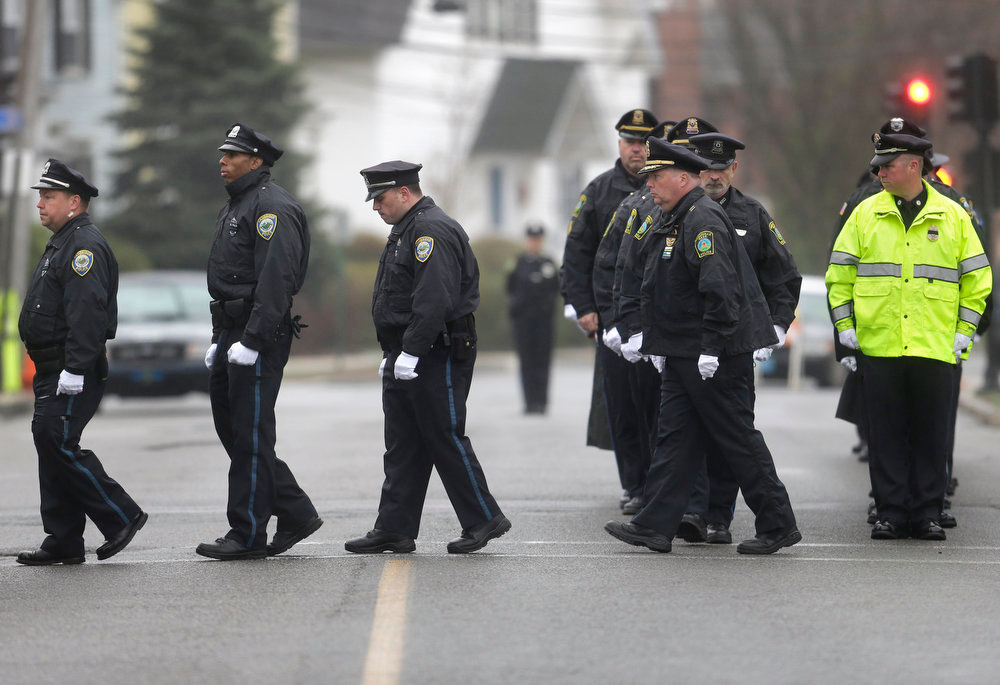 . Police officers march in formation as they enter St. Patrick\'s Church, in Stoneham, Mass., before a funeral Mass for Massachusetts Institute of Technology police officer Sean Collier Tuesday, April 23, 2013. Collier was fatally shot on the MIT campus Thursday, April 18, 2013. Authorities allege that the Boston Marathon bombing suspects were responsible. (AP Photo/Steven Senne)
