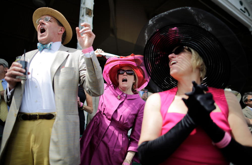 Description of . Jim and Marianne Welch along with Patty Johnson, right, celebrate during the eighth race before the 140th running of the Kentucky Derby horse race at Churchill Downs Saturday, May 3, 2014, in Louisville, Ky. (AP Photo/David Goldman)