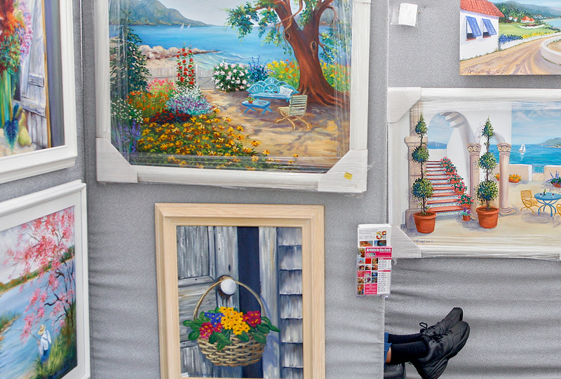 "012415 - DELRAY BEACH - Incorporated in 1965, 2015 marks the 50th anniversary for the The Delray Art League. Pictured are paintings and feet belonging to artist, and Delray Art League.    ""outdoor show director"" Gay Williamson,  Gay was reading a book in an alcove she had made to avoid heavy winds Saturday morning at Veteran's Park.  Photo by Tim Stepien"