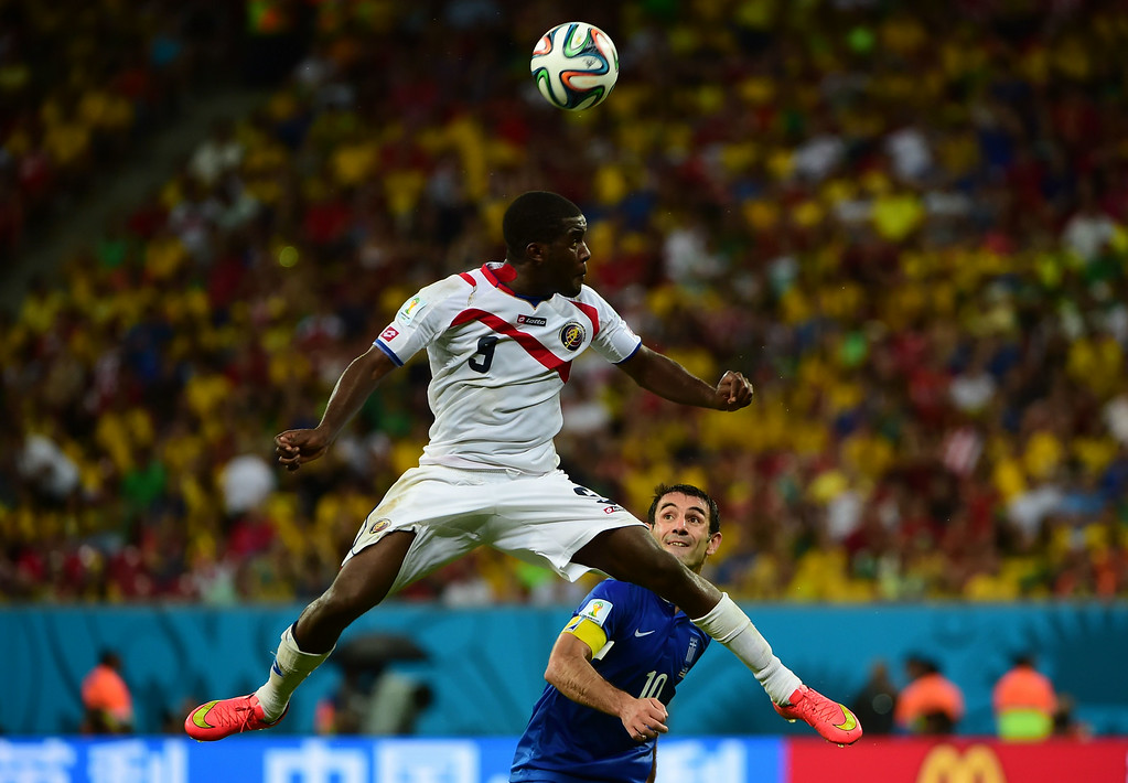 . Costa Rica\'s forward Joel Campbell heads the ball next to Greece\'s midfielder Giorgos Karagounis (back) during the round of 16 football match between Costa Rica and Greece at Pernambuco Arena in Recife during the 2014 FIFA World Cup on June 29, 2014. AFP PHOTO / RONALDO SCHEMIDT