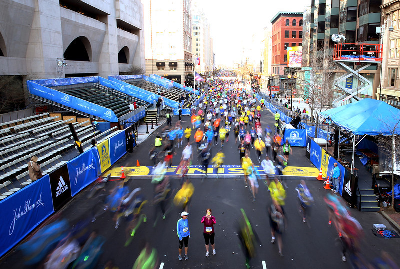 . Runners cross the finish line of the Boston Marathon as part of the 2014 B.A.A. 5K race course on April 19, 2014 in Boston, Massachusetts.  (Photo by Alex Trautwig/Getty Images)