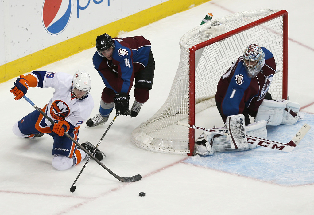 . New York Islanders center John Tavares, left, reaches out for puck as Colorado Avalanche defenseman Tyson Barrie, center, defends and goalie Semyon Varlamov, of Russia, watches the second period of an NHL hockey game in Denver on Friday, Jan. 10, 2014. (AP Photo/David Zalubowski)