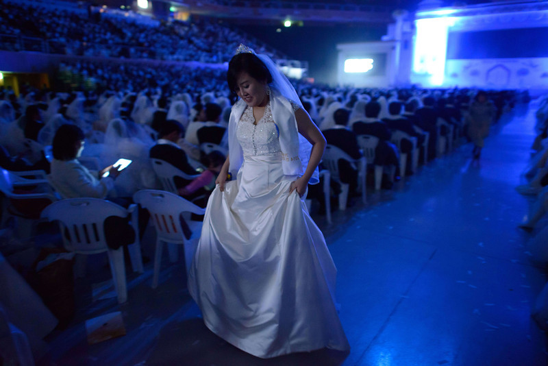 ". A bride walks between aisles during a mass wedding event held by the Unification Church in Gapyeong on February 12, 2014. Unification Church members forming 2500 couples from 52 countries were married in a mass wedding in South Korea -- only the second such event since the death of their ""messiah\"" and controversial church founder Sun Myung Moon. (ED JONES/AFP/Getty Images)"