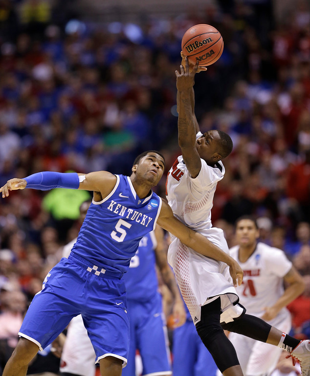 . Kentucky\'s Andrew Harrison (5) and Louisville\'s Terry Rozier go after a loose ball during the first half of an NCAA Midwest Regional semifinal college basketball tournament game Friday, March 28, 2014, in Indianapolis. (AP Photo/David J. Phillip)