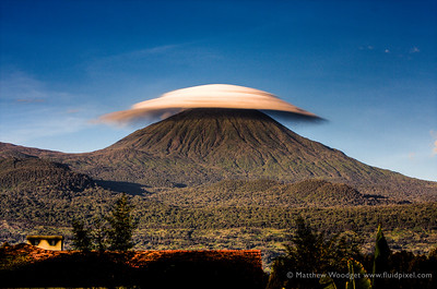 **Provided for Prints more print options** .e.g  Use this version to print in standard size then you will need to cut to size and frame -- A lenticular cloud hangs in the still morning air over Karisimbi, Volcanoes National Park in Rwanda. Straddling The Congo border these mountains are the home to some of our closest ancestors and the almost extinct, always majestic Mountain Gorillas.