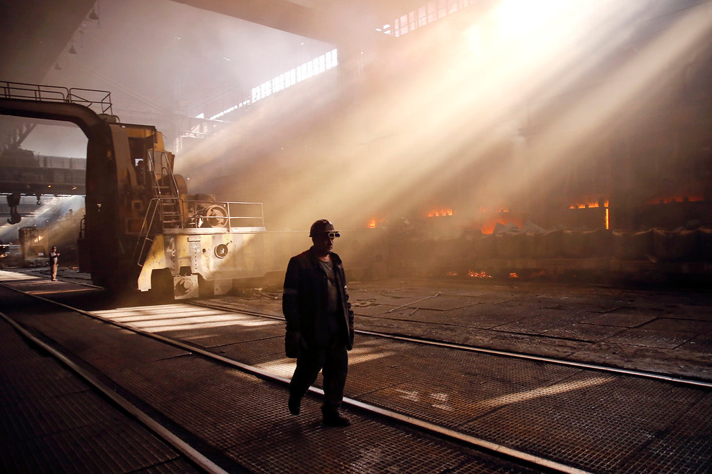 . An employee walks through the scrap metal area as sunlight streams through the windows at the Zaporizhstal steel plant, owned and operated by Metinvest BV, at their site in Zaporizhzhya, Ukraine, on Monday, Oct. 14, 2013. Metinvest BV, Ukraine\'s largest steelmaker, last year acquired 49.9% in steelmaker Zaporizhstal a manufacturer of semi-finished steel products, including hot and cold-rolled plates and coils. Photographer: Vincent Mundy/Bloomberg
