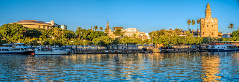 The Guadalquivir river and some of the main landmarks of Seville: Teatro de la Maestranza (left), Giralda tower (center, on the background) and Torre del Oro (Tower of Gold, right. foreground). High resolution panorama.
