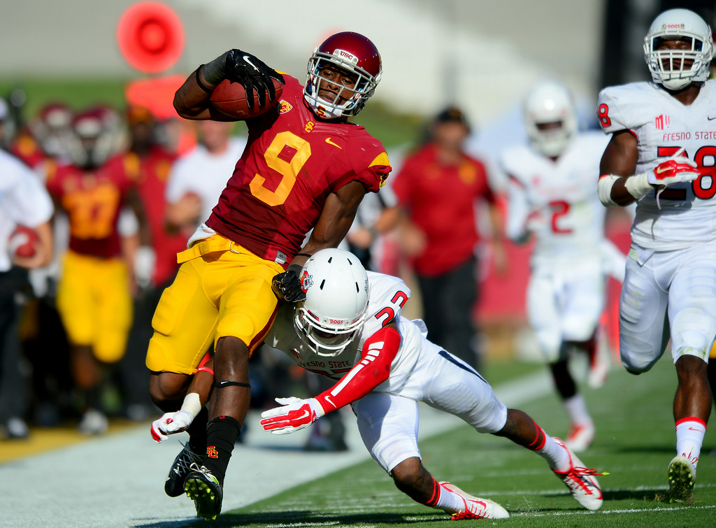 . USC WR JuJu Smith runs up the sidelines for a 52-yard pass reception in the first-quarter as Fresno State\'s Bryan Harper makes the tackle, Saturday, August 30, 2014, at the L.A. Memorial Coliseum. (Photo by Michael Owen Baker/Los Angeles Daily News)