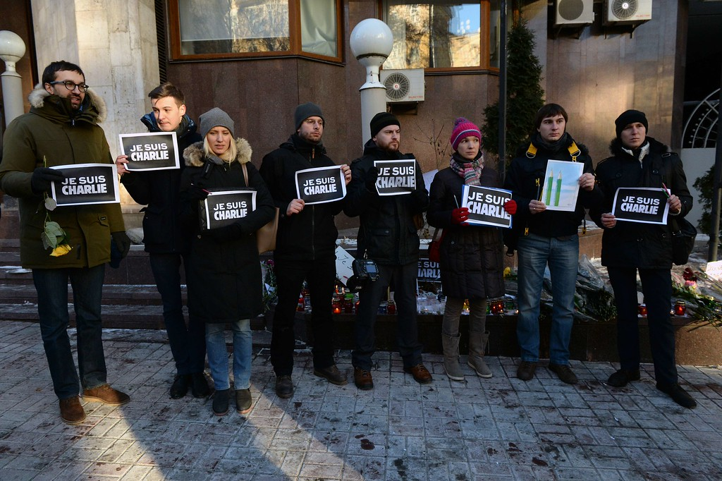". Ukrainian journalists hold placards reading in French ""I am Charlie\"" in front of the French embassy in Kiev on January 8, 2015, in tribute to the twelve people killed the day before in an attack by two armed gunmen on the offices of French satirical newspaper Charlie Hebdo in Paris. A stunned and outraged France was in mourning today, as security forces desperately hunted two brothers suspected of gunning down 12 people in an Islamist attack on a satirical weekly. AFP PHOTO / VASILY MAXIMOV/AFP/Getty Images"