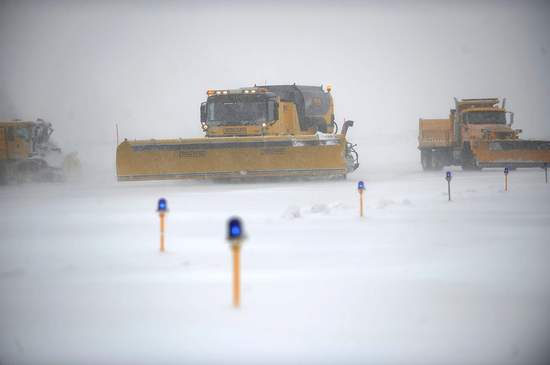 . Snow removal crews clear a runway at Denver International Airport on Sunday, February, 24, 2013. A major winter storm caused the cancellation of nearly 200 flights at DIA on Sunday. Seth A. McConnell, The Denver Post