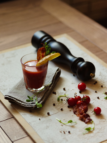 Organic cherry tomatoes, spicy peppercorns, herbs and pepper mill on a white fabric on a table. A glass of Bloody Mary with bacon and piece of potato on a top of a glass on a blurred background.