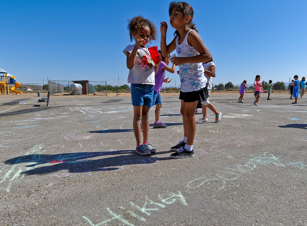 . First-graders Ariel Gibbs, 6, left, and Carmela Morales, 7, right blow bubbles during a fun activity on the final day of school at Hinkley School in Hinkley, Calif. on Thursday, June 6, 2013. Hinkley School is closing for good at the end of the 2012-2013 school year. (Rachel Luna / San Bernardino Sun)