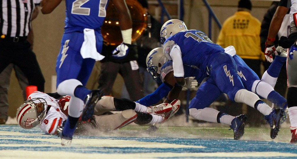 . UNLV quarterback Caleb Herring, left, falls into the end zone for a touchdown as Air Force defensive back Dexter Walker, back right,, and linebacker Reggie Barnes cover in the first quarter of an NCAA football game at Air Force Academy, Colo., on Thursday, Nov. 21, 2013. (AP Photo/David Zalubowski)
