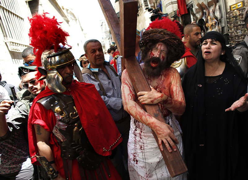 """. A Christian pilgrim reenacts the crucifixion of Jesus Christ along the path where Jesus walked, now known as the \""""Via Dolorosa\"""", or the \""""Way of Suffering\"""", on Good Friday in Jerusalem\'s Old City on April 18, 2014. Christian pilgrims mark the anniversary every year by walking from the Garden of Gethsemane on the Mount of Olives to the Church of the Holy Sepulchre in the middle of the Old City, an ancient sprawling shrine which Orthodox and Catholic Christians believe was built on the original site of the crucifixion and burial of Jesus.  (THOMAS COEX/AFP/Getty Images)"""