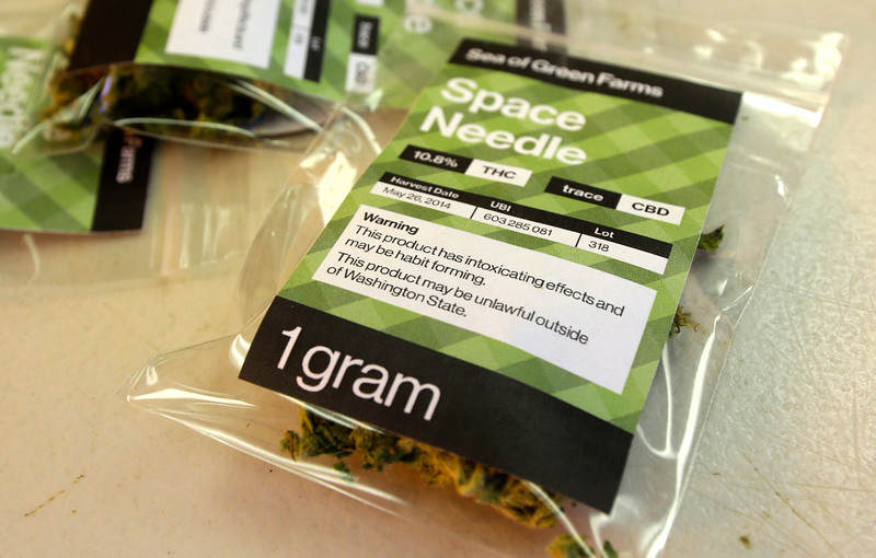 ". This July 1, 2014, photo shows a one-gram packet of a variety of recreational marijuana named ""Space Needle\"" during packaging operations at Sea of Green Farms in Seattle. Each packet is labeled with the percentage of THC, a lot number, and warning messages. (AP Photo/Ted S. Warren)"