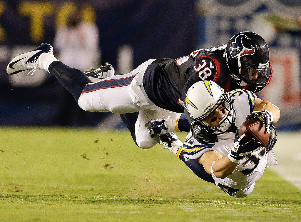 . San Diego Chargers running back Danny Woodhead dives for extra yard under pressure from Houston Texans free safety Danieal Manning during the first half of an NFL football game Monday, Sept. 9, 2013, in San Diego. (AP Photo/Gregory Bull)