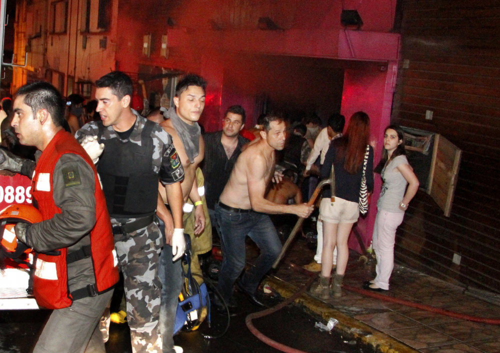 . People react outside the Kiss nightclub as a fire burns inside in Santa Maria, Brazil, Sunday, Jan. 27, 2013. A fast-moving fire roared through the crowded, windowless Kiss nightclub in this southern Brazilian city early Sunday, killing more than 230 people. Many of the victims were under 20 years old, including some minors. (AP Photo/Deivid Dutra, Agencia Brasil)