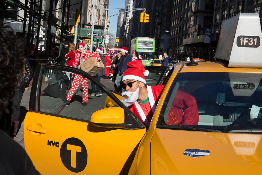 . A man dressed in a holiday theme  costume enters a taxi during SantaCon, Saturday, Dec. 13, 2014, in New York.  SantaCon organizers retained lawyer Norman Siegel  last week as part of an effort to tame the excesses of the daylong party.  Siegel said the government cannot ban SantaCon. But he said the government can reasonably regulate the event. (AP Photo/John Minchillo)