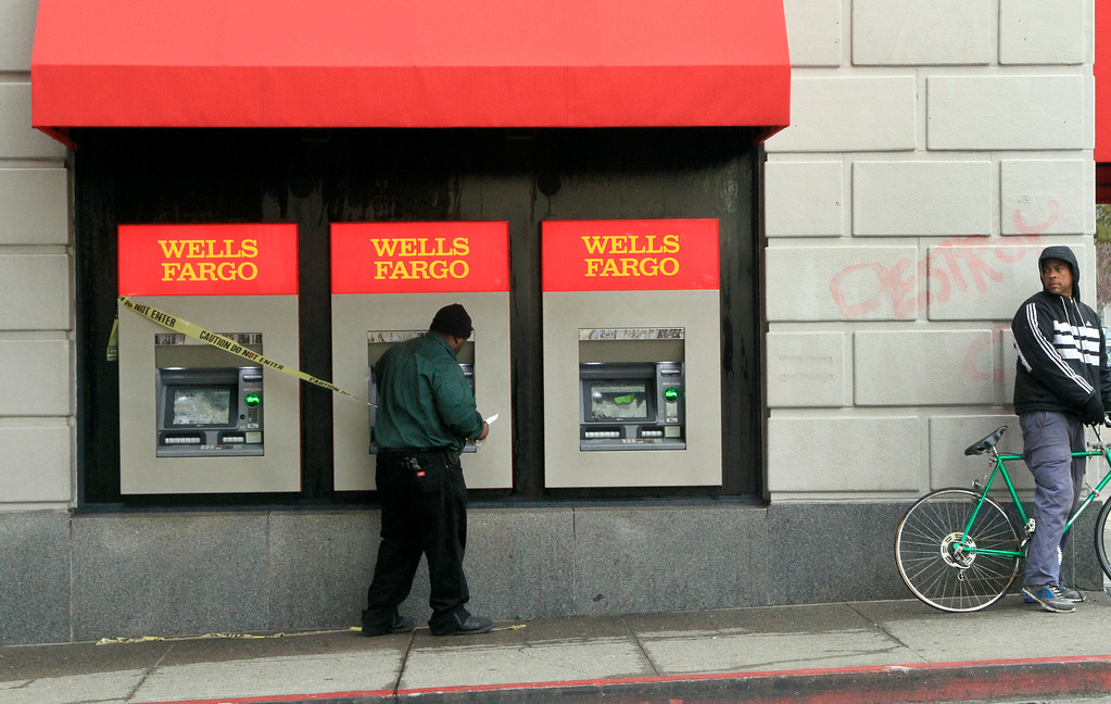 . A worker puts up caution tape along the broken ATMs at the Wells Fargo bank branch on Shattuck Avenue in Berkeley, Calif., on Monday, Dec. 8, 2014, after another night of protest and vandalism.   (Laura A. Oda/Bay Area News Group)