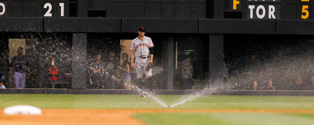 . San Francisco Giants\' Hunter Pence stands in right field when the sprinklers came on for a few seconds during the fourth inning of a baseball game against the Colorado Rockies, Monday, Aug. 26, 2013, in Denver. A grounds keeper said that the sprinklers came on due to back pressure on the valves. (AP Photo/Barry Gutierrez)