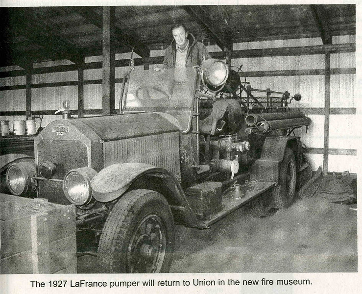 Current Fire Chief Fred Fretz proudly displays this antique pumper which currently resides at the Liberty Hall Fire Museum.