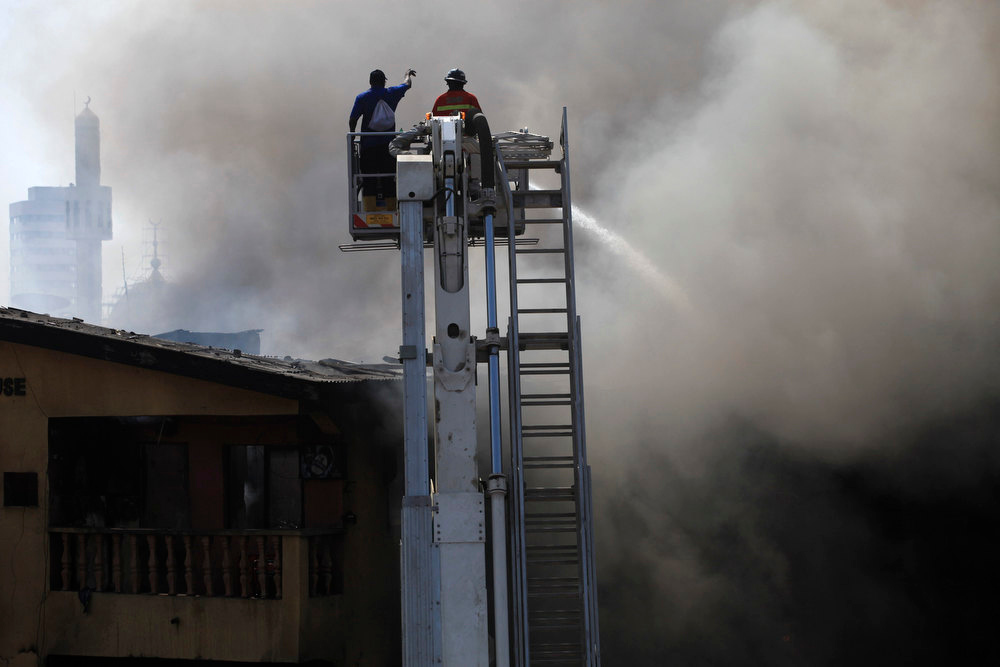 Description of . Firefighters use a crane to try extinguish a fire after fireworks stored in a building exploded in a densely populated area in the Isale Eko district of Nigeria's commercial capital of Lagos December 26, 2012.REUTERS/Akintunde Akinleye