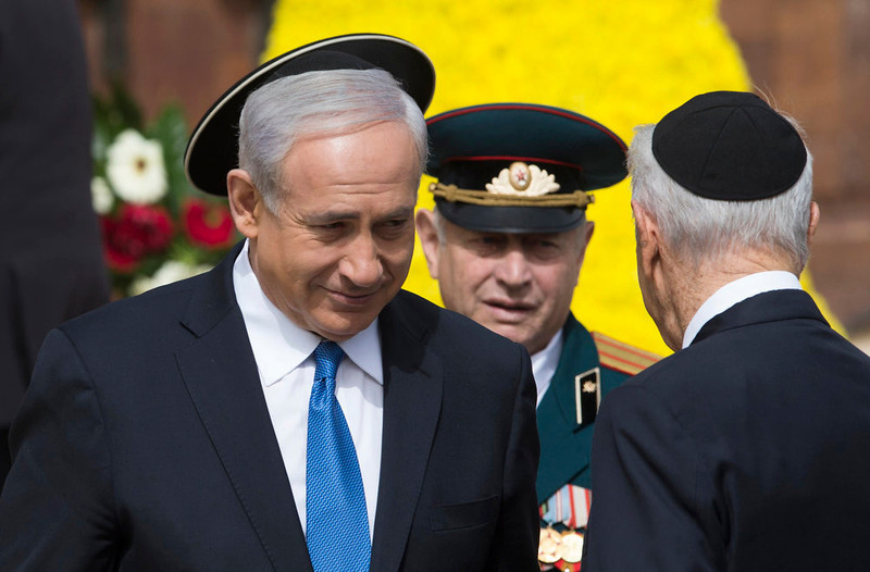 . Israel\'s Prime Minister Benjamin Netanyahu (L) and President Shimon Peres (back to camera) attend a wreath-laying ceremony marking Israel\'s annual day of Holocaust remembrance, at Yad Vashem in Jerusalem April 8, 2013. Israel on Monday commemorates the six million Jews killed by the Nazis in the Holocaust during World War Two. REUTERS/Ronen Zvulun