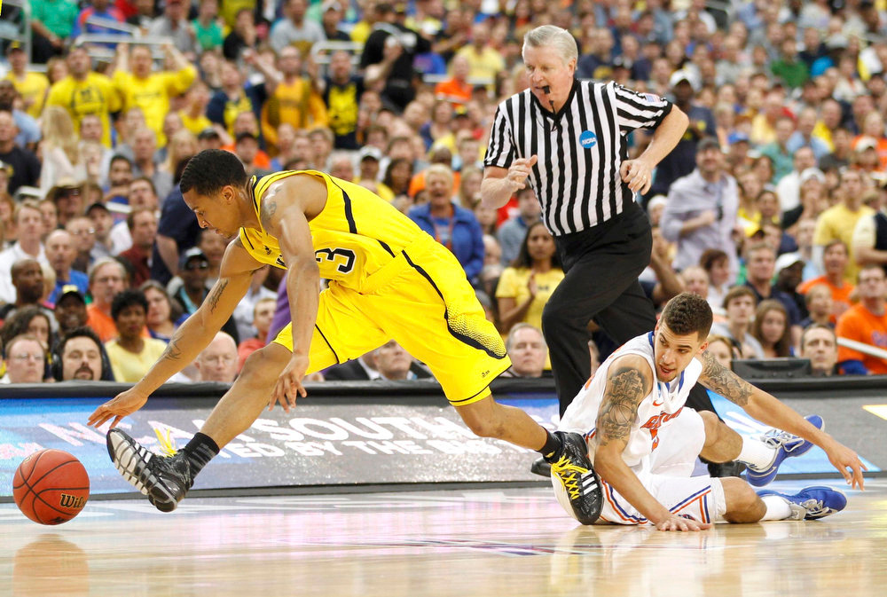 . Michigan Wolverines guard Trey Burke (L) battles for the ball against Florida Gators guard Scottie Wilbekin in their South Regional NCAA men\'s basketball game in Arlington, Texas March 31, 2013. REUTERS/Mike Stone