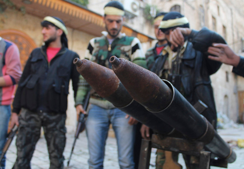 . Members of the Free Syrian Army stand beside a rocket launcher, in the old city of Aleppo March 2, 2013. Picture taken March 2, 2013. REUTERS/Saad Abobrahim