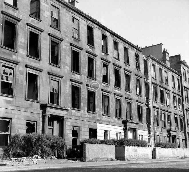 Abbotsford Place, east side.  July 1973   Abbotsford Place, more than anywhere else in the Gorbals, anywhere else in the city, had an air of faded grandeur. It was a ruined, down-and-out aristocrat of a street. Built, without uniformity but harmoniously enough, between 1820 and 1830, it was to be a douce New Town for professional people, just a step across the river from the city. The width of the street was generous, and each flat had an interior wc, which was an exceptional luxury in these days, and generally five spacious apartments, the dining room around 22ft by 16ft. For 30 or 40 years it was a 'good' address, but the coming of the railway gave the middle classes the freedom to move further afield, to leafy suburbs far from the city slums, and the decline of Abbotsford Place (and Cumberland St and Nicholson St and others) was rapid. The size of the flats meant they were highly suitable for multiple occupancy, and successive waves of immigrants, Irish, eastern European Jews, Italians, and more recently Asians found in them a foothold on the property ladder.  These tenements were soundly built, and could have been refurbished. The lack of imagination which led to their removal was shameful.