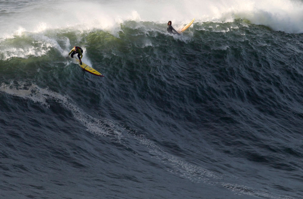 Description of . US surfer Garrett McNamara, left, makes a take off on a wave at Praia do Norte beach in Nazare, Portugal, Tuesday, Jan. 29, 2013. McNamara is said to have broken his own world record for the largest wave surfed when he caught a wave reported to be around 100ft off the coast of Nazare on Monday. If the claims are verified, it will mean that McNamara, who was born in Pittsfield, Massachusetts but whose family moved to Hawaii's North Shore when he was aged 11, has beaten his previous record, which was also set at Nazare, of 78 feet  in November 2011. (AP Photo/Francisco Seco)